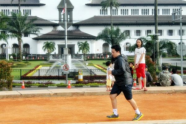Seorang warga Bandung berolahraga lari mengelilingi lapangan Gasibu Bandung. (Nabila Ghina Fadhila/JUMPAONLINE)