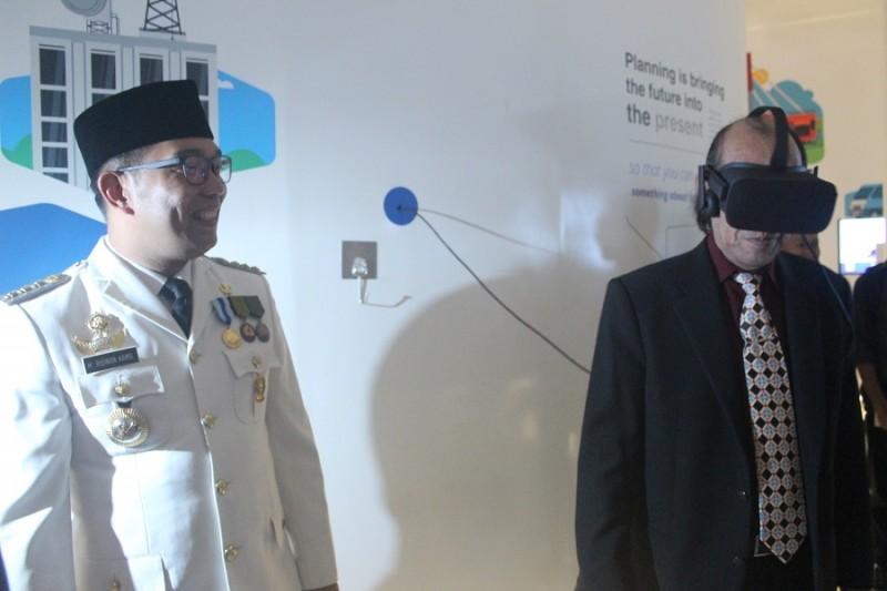 Ridwan Kamil sedang memperkenalkan Virtual Reality sebagai salah satu teknologi yang ada di gedung Bandung Planning Gallery kepada ketua DPRD Kota Bandung, Isa Subagdja. (Gita Gisela/JUMPAONLINE)